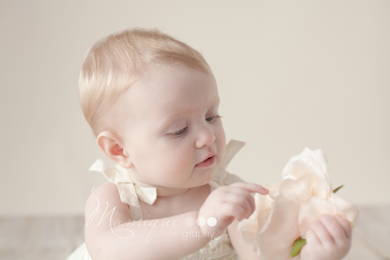 Pretty baby girl inspecting flowers wearing a cream dress