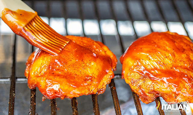 brushing chicken thighs with barbecue sauce