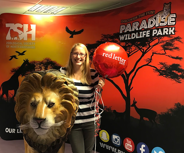 Me posing with a lion and a red balloon in front of a sign advertising Paradise Wildlife Park
