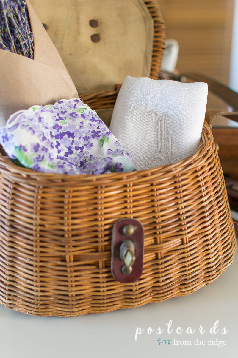 small fishing creel basket with lavender and linens inside