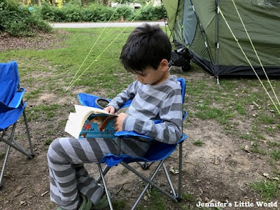 Child reading by a tent