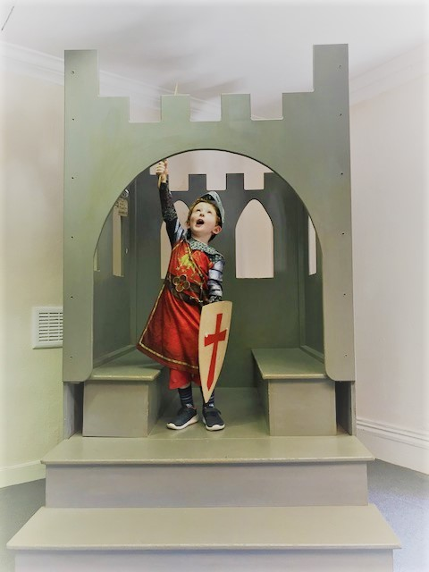 Little boy dressed as a knight holding a sword and holding a sword in the air