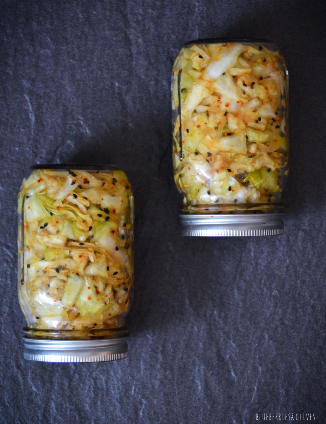 KIMCHI IN TWO GLASS JARS ON A DARK BACKGROUND