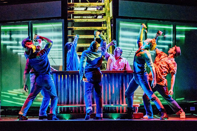 dancers in mechanic overalls stood at a bar on stage