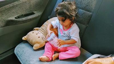 gambar Aina berusia setahun sembilan bulan sedang bermain dengan bekas makanan dalam kereta Proton Persona bersama patung kucing.