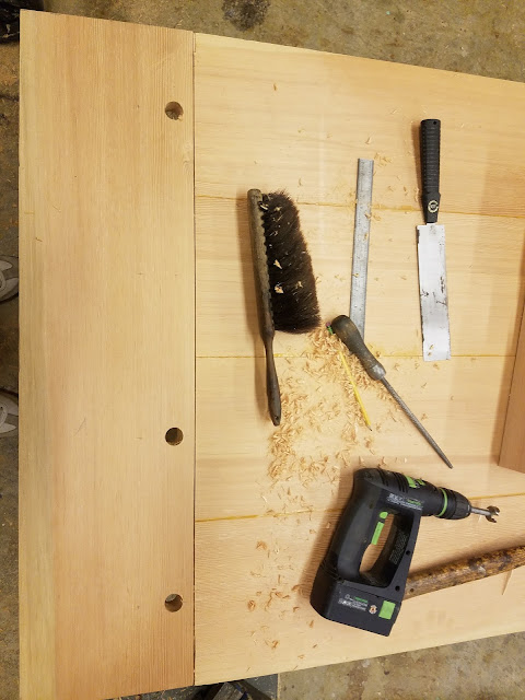holes are drilled through the breadboard-tabletop assembly before enlarging the tenon holes into slots.
