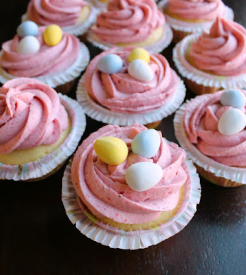 cupcakes with swirls of strawberry buttercream and mini chocolate eggs on top