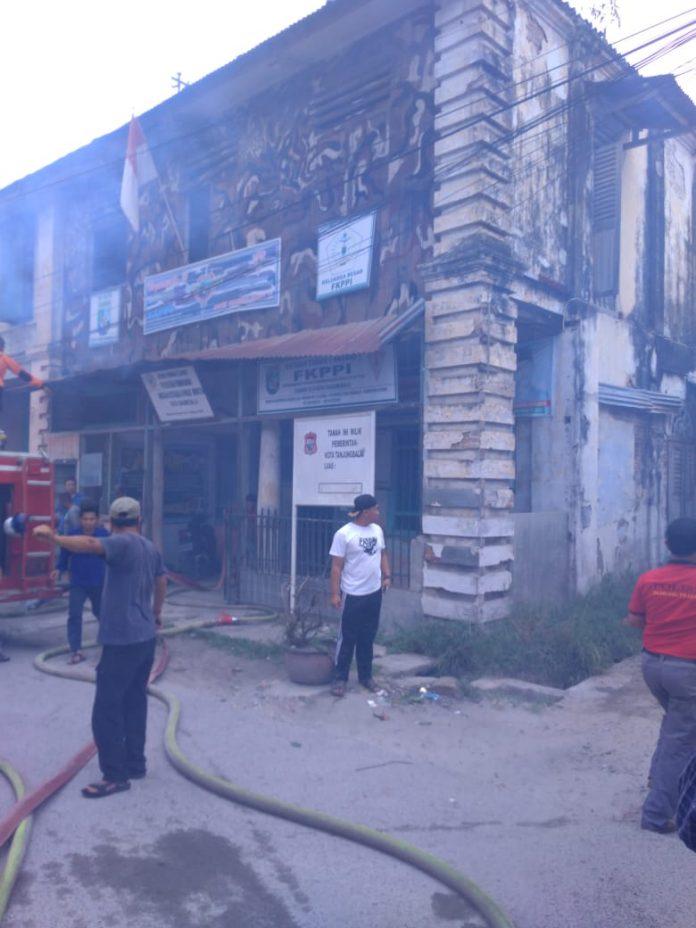 Petugas pemadam kebajaran memadamkan api di Kantor FKPPI Tanjungbalai yang terbakar.