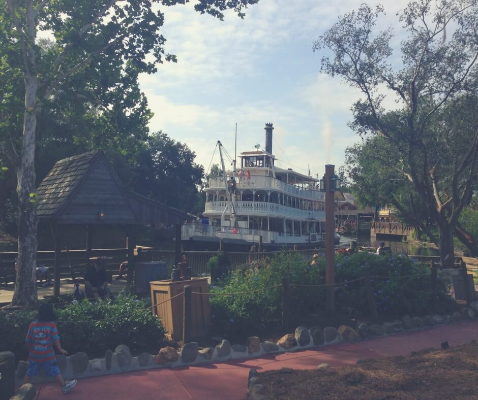 The Liberty Square Riverboat at Magic Kingdom sails. Trees line the bank in the background of the photo and bushes line the foreground. The colonial-american inspired paddler wheeler sails the river, heading towards the camera. There is a young boy in closest to the camera, with his back to the camera, wearing a red and green striped t-shirt and blue shorts. He looks like he is skipping with excitement. The sun shines in a cloudless blue sky.