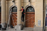 a man playing a violin walks along a rope that runs between two braces that he has set up in front of the entrance to a building.