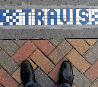 Travis Street signage on sidewalk in blue and white tiles