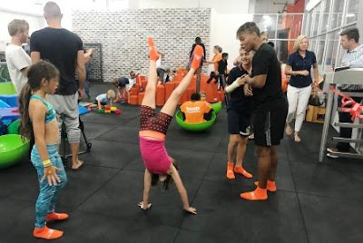 Girl doimg hand stands while trainer is looking on