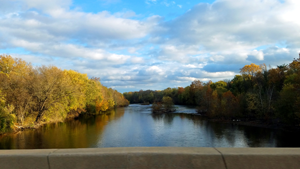 image of a river lined on both sides by trees in glorious colors