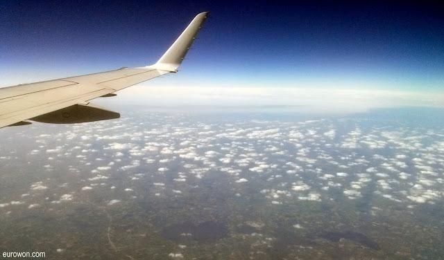 Avión sobrevolando nubes y lagos