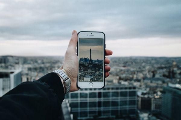 Pessoa fotografa torre Eiffel usando celular com chip internacional