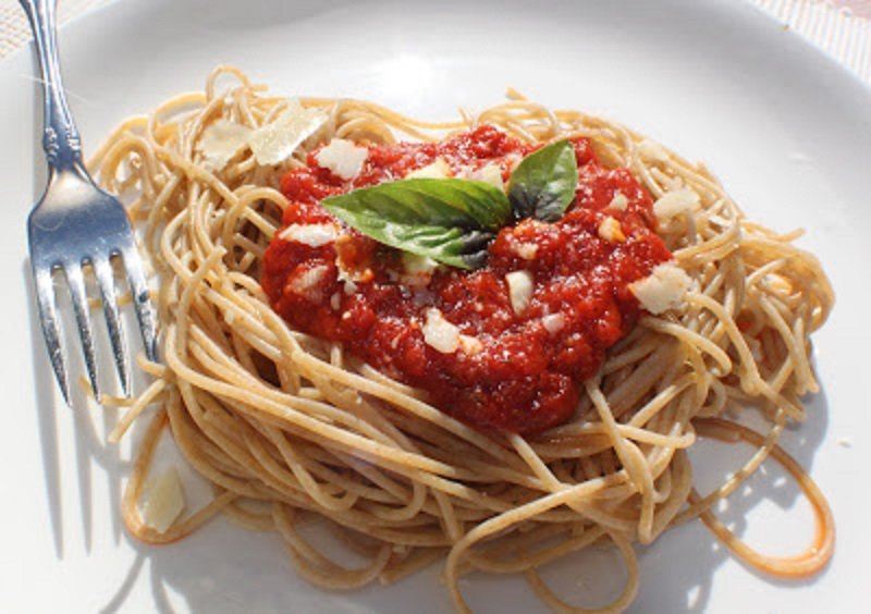 Delicious homemade simple tomato sauce called marinara with all fresh ingredients over spaghetti sprinkled with cheese on a white plate some garlic herbs in a white plate with a fork