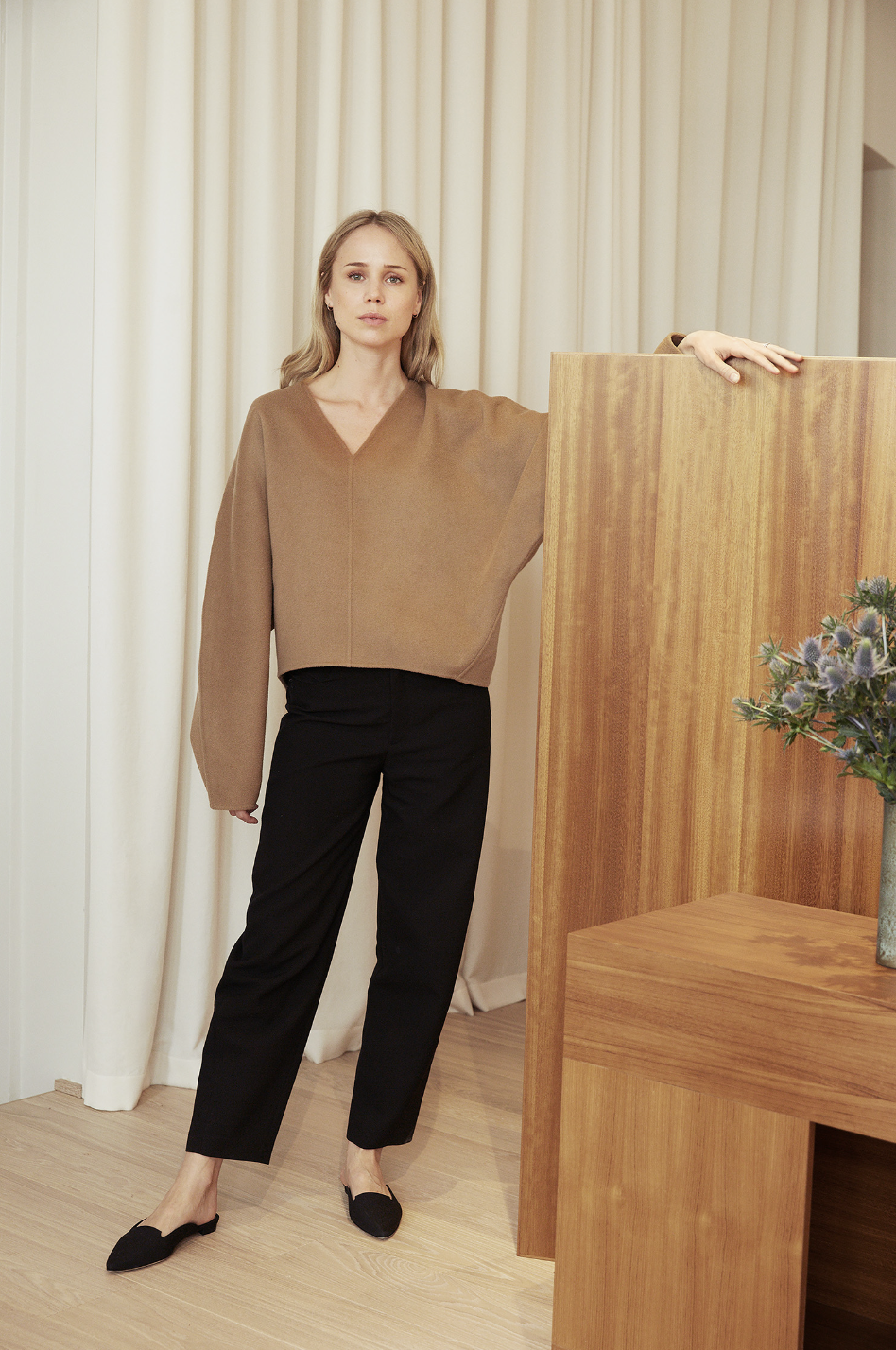3-Piece Office Outfit for Spring — Elin Kling in a camel v-neck sweater, black pants, and black mule flats.
