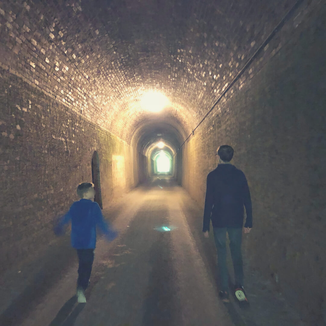 "Two boys walk through a dark tunnel, light at the end of the tunnel shines brightly. Image for ""How to tackle the challenges of Parenting""."