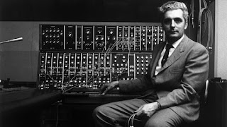 American inventor Robert Moog smiling as he rests his arms atop his pioneering Moog synthesizer, with a keyboard and electronic circuits, circa 1970. Jack Robinson archive