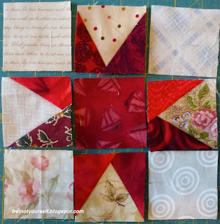 Nine 2.5-inch square patches of red and cream are laid out to form a star