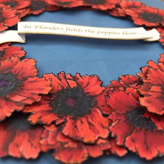 "3D detail of banner, which says ""In Flanders Fields the poppies blow"""