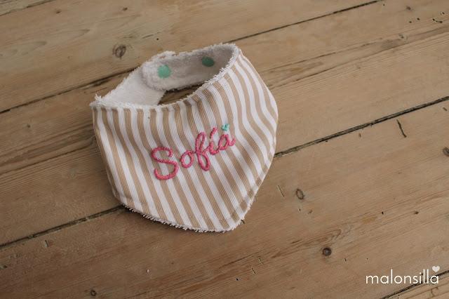 Baberos personalizado con doble cierre de clip sobre fondo de madera con el nombre de Sofía by malonsilla