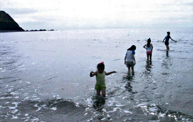 4 girls paddling in the sea standing in height order.