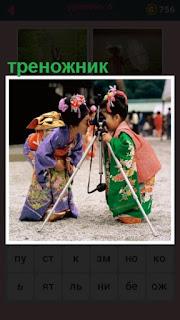 две девочки в кимоно стоят около треножника с фотоаппаратом