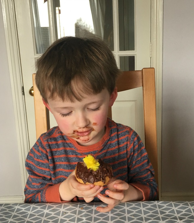 boy-holding-cup-cake-with-chocolate-around-his-mouth