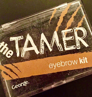 A large rectangular box with a bright lid that has streaks of different shades of brown on it with Tamer in bold thick white font with eyebrow kit in smaller white font underneath on a bright background.