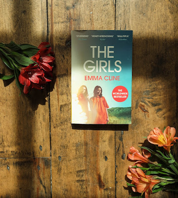 Typewriter Teeth The Girls Emma Cline Book Review , image of the novel surrounded by flowers