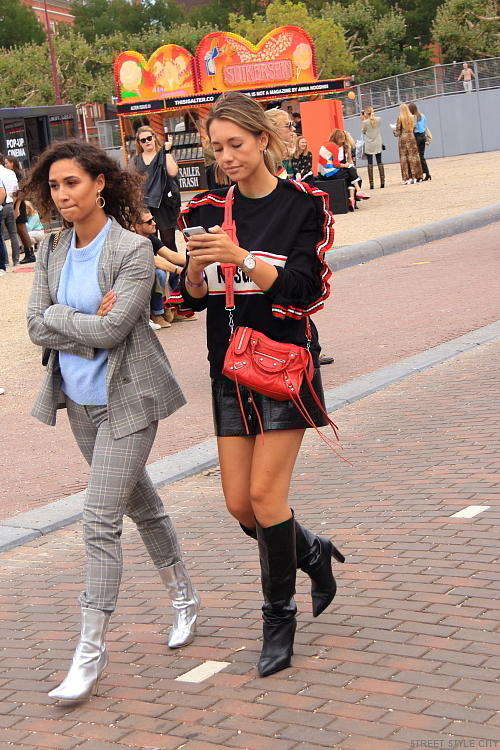 female sexy legs wearing leather high heeled boots and leather mini skirt in the street of amsterdam. candid street style fashion in the city