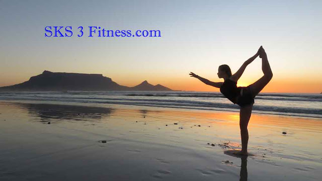 A girl showing How to do Dancer Yoga Pose / Natrajasana at the beach / sea-shore