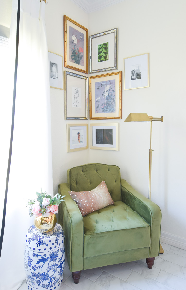 This olive green vintage tufted chair adds a pop of color to a silver and gold corner gallery wall and reading nook in this stunning master bedroom.