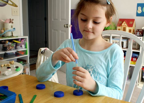 Tessa used recycled milk bottle caps for the wheels of her sail car. I pre-punched the holes ahead of time.