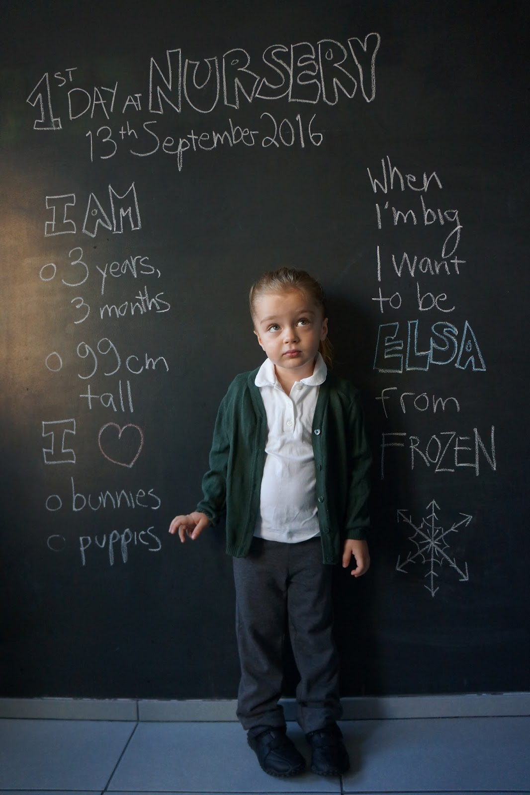 toddler in front of blackboard wall