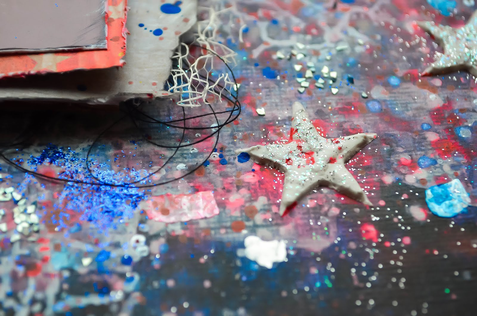 Fourth of July/Independence Day fireworks mixed media layout in red, white, and blue using texture paste and chipboard stars with encrusted jewel technique, glitter and glass glitter, mica fragments, bakers twine, texture paste and stenciling.