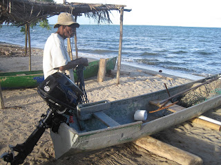 Belizean fisherman with outboard-powered dugout canoe