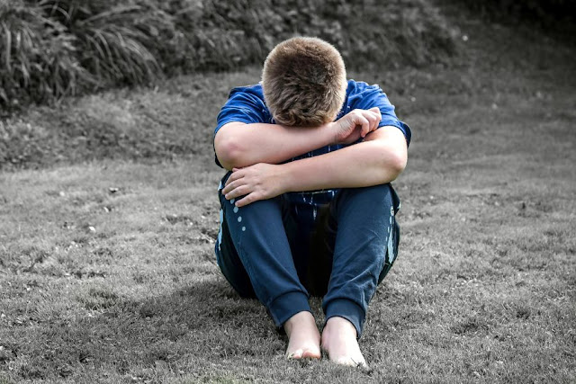 Photo of a boy crying while sitting on the ground