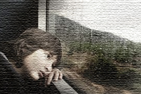 A sad child looking out of a window