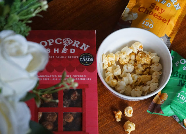 image shows a flat lay of popcorn shed products and artificial flowers