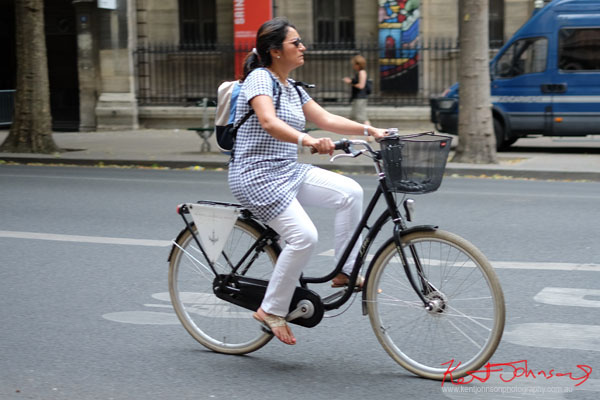 Woman in blue gingham top and white pants on black ladies bike. Paris photos by Kent Johnson for Street Fashion Sydney.