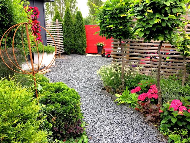 Entré inn i hagen omkranset av blomsterbed og små Agnbøkstrær. Trädgårdsrundorna