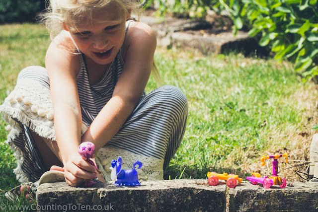 A young girl playing with little Vampirina figures in a garden