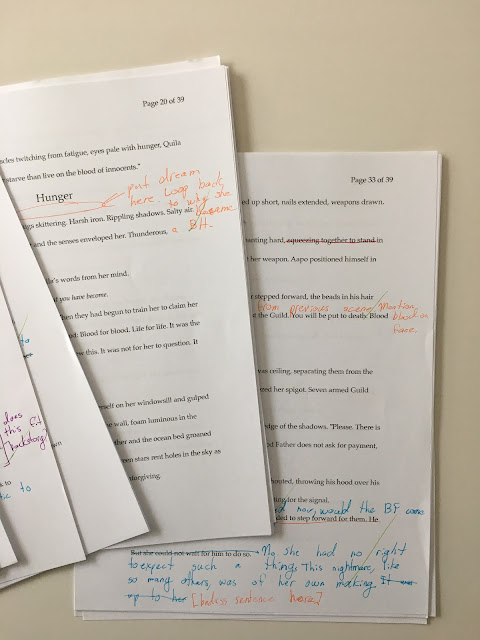 Editing notes on multiple pages. Some notes in orange ink, some questions in purple ink, some crossed out sentences in red ink, some new sentences written in the margins in blue ink.