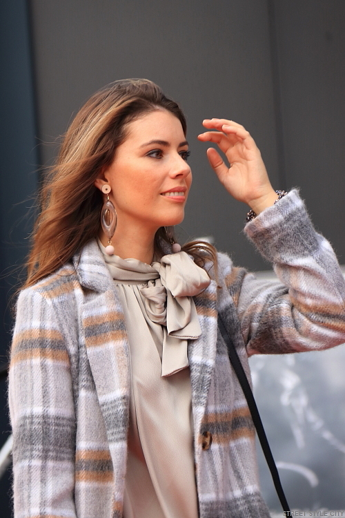 Beautiful dutch brunette woman wearing checkered winter coat in the street. Streetstyle fashion outfit.