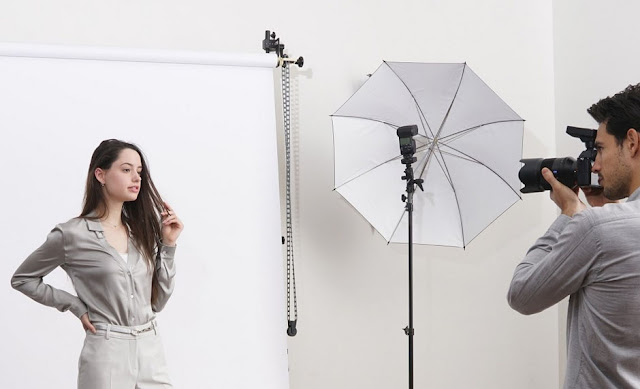 A model posing in front of a photographer using a Sony digital camera and Sony flashgun