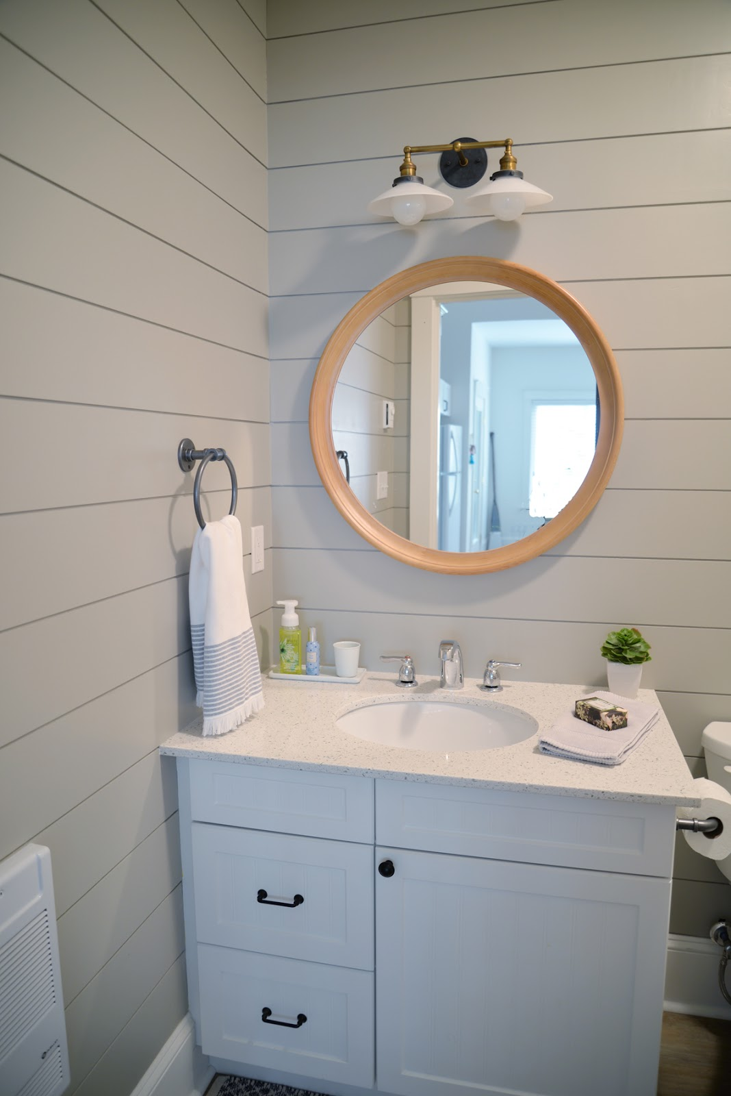 grey painted shiplap in the bathroom, round wood mirror, milk glass sconce | Ramblingrenovators.ca