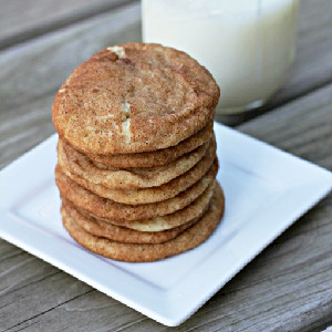 snickerdoodles on white plate with glass of milk in background