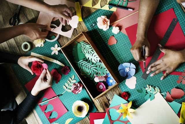 Paper crafts being done around a table with lots of different hands making things